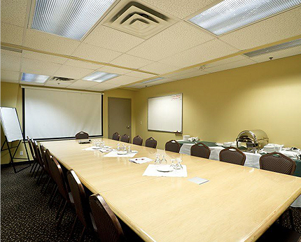 meeting room with board table, chairs, and projector screen