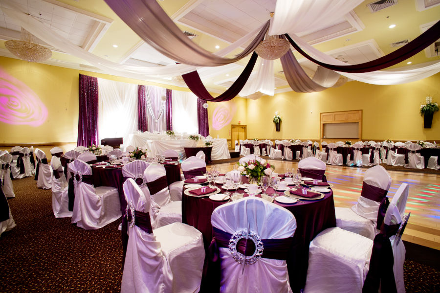 hall with purple wedding and social dinner decorations